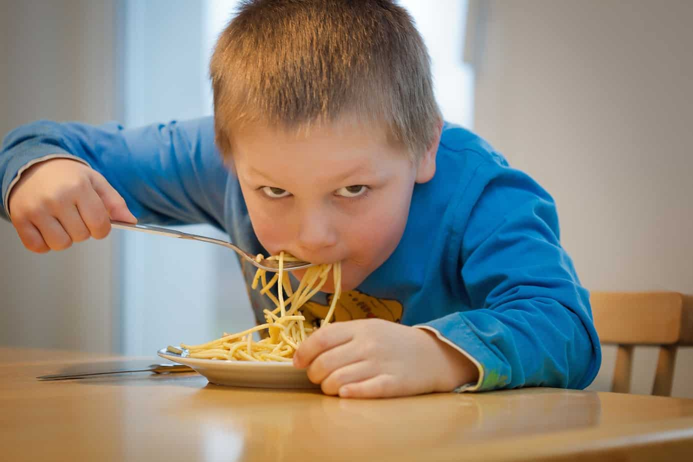 young boy eating spaghetti at a table