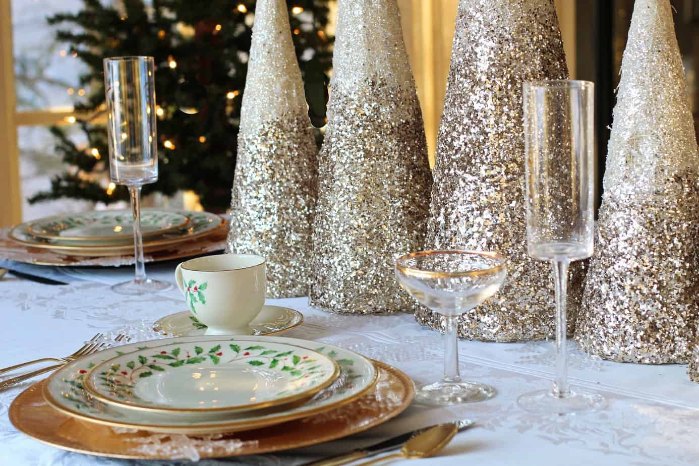 Place setting Lenox china with holly and gold rim on table decorated for the holidays.
