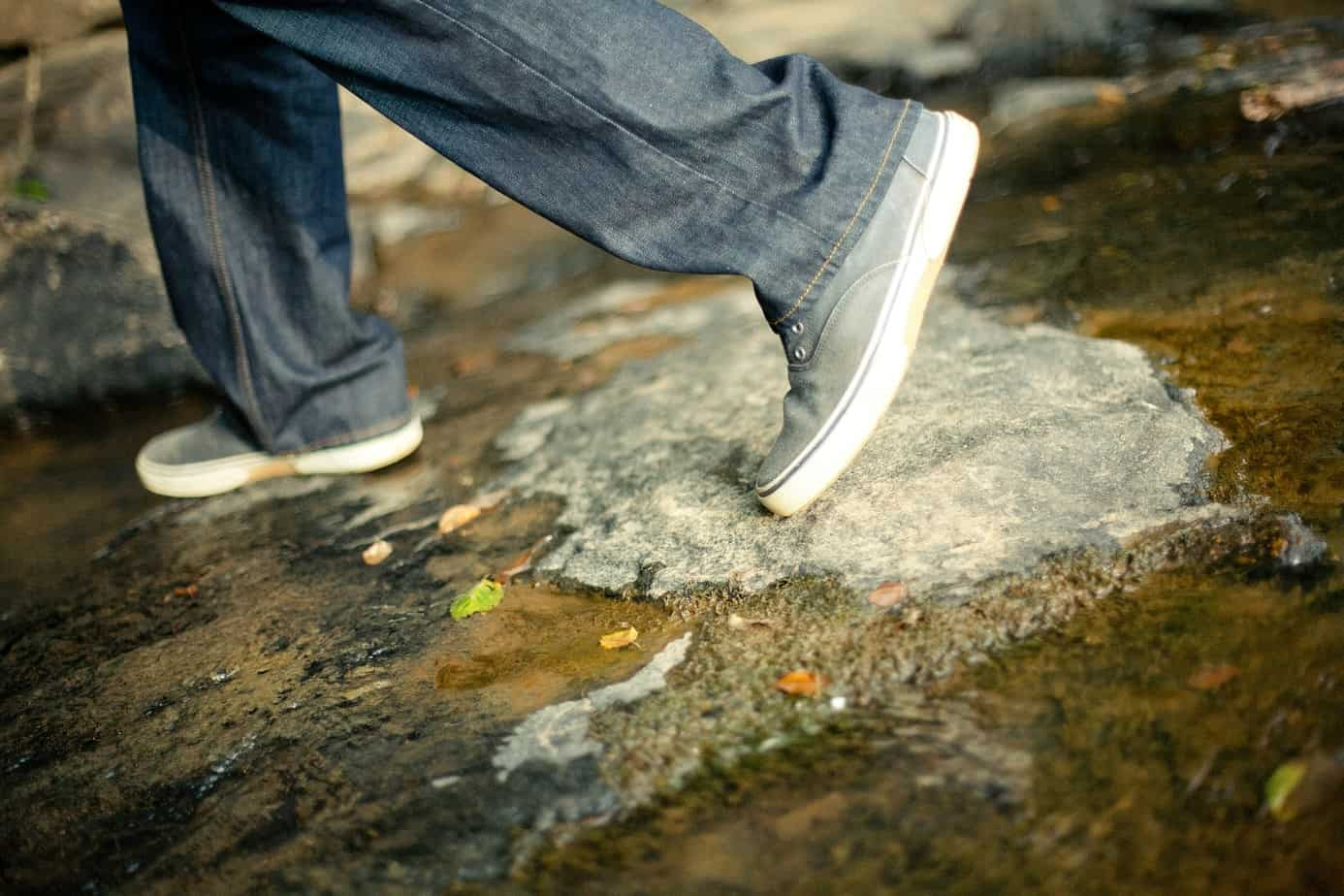 person walking in sneakers and jeans