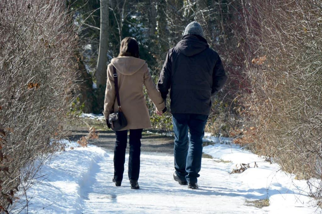 man and woman walking hand in hand down snowy path
