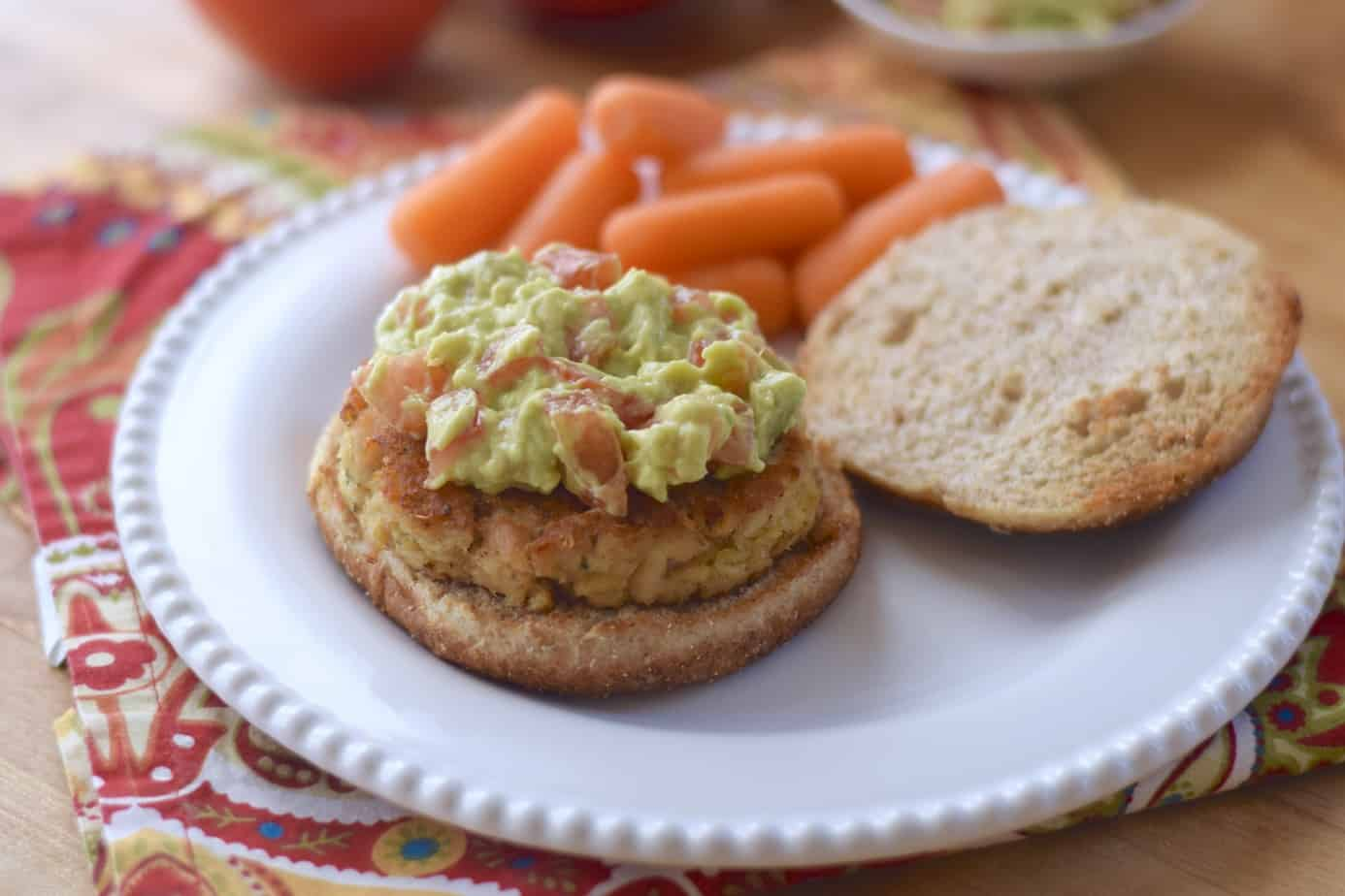 tuna burger topped with smashed avocado and tomato on a whole grain bun on plate with baby carrots