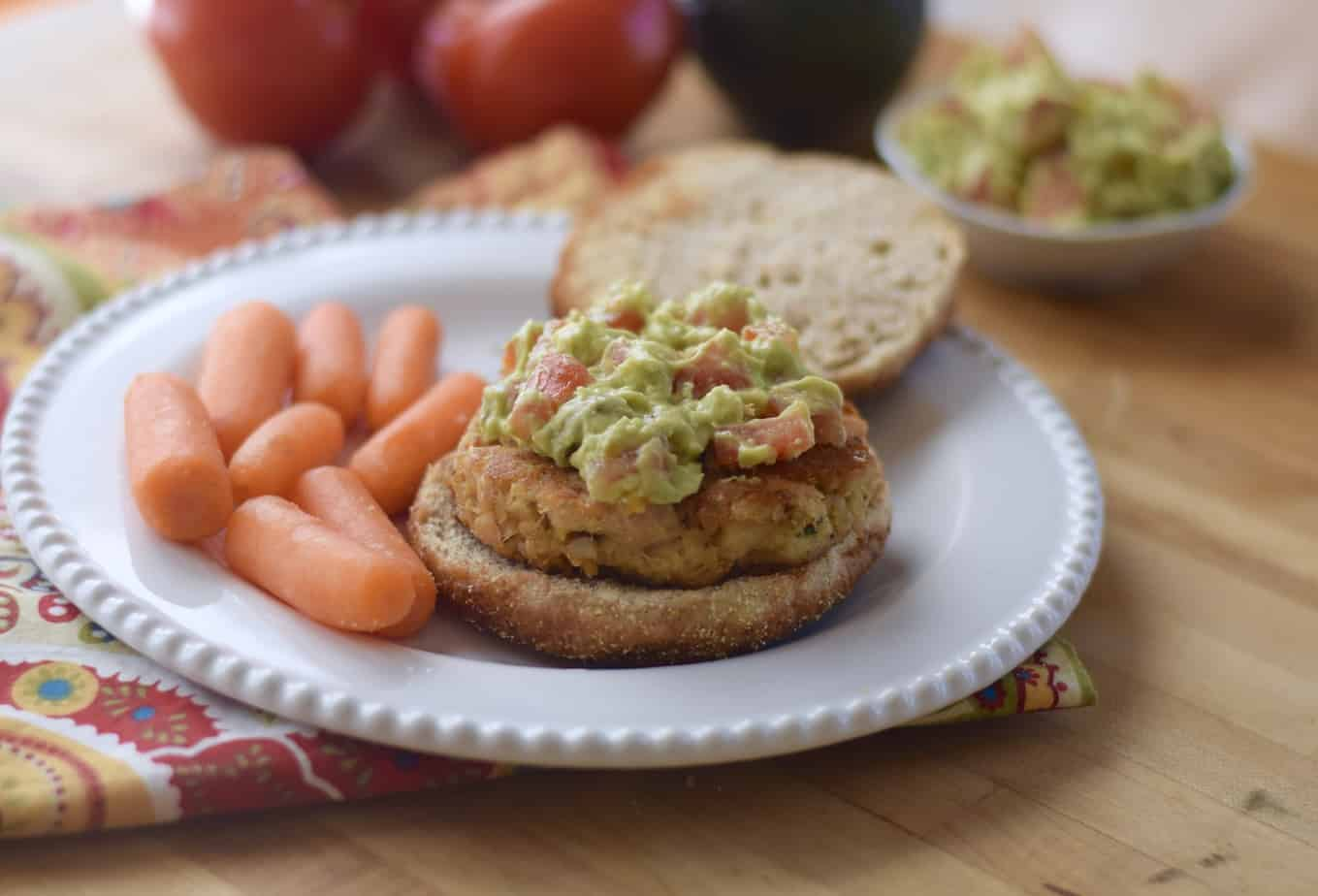 tuna burger on bun topped with avocado-tomato mixture