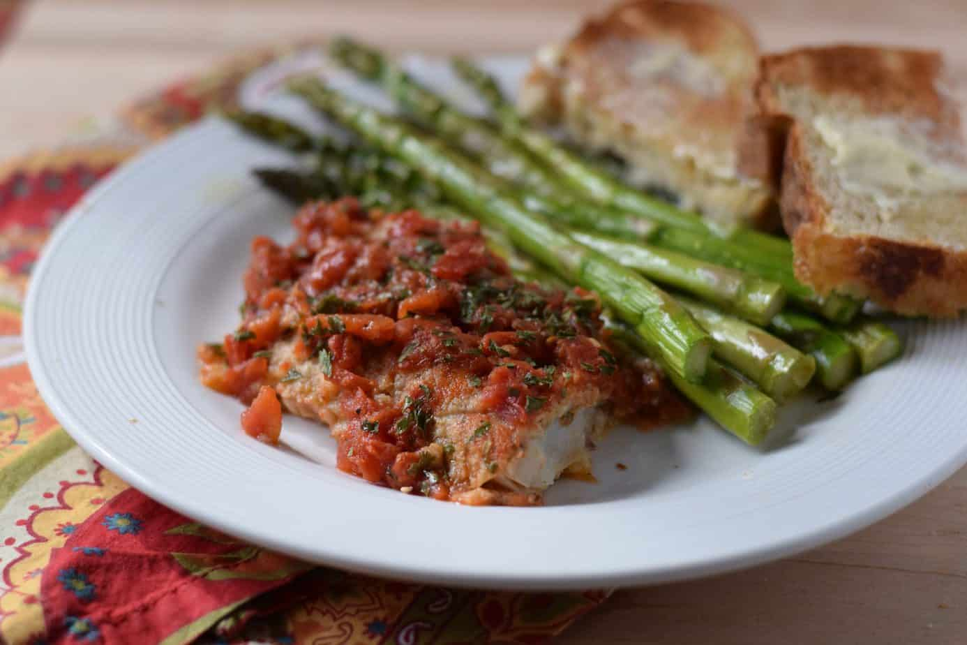 Baked fish cooked in a foil packet topped with tomatoes next to roasted asparagus and two slices of whole wheat bread and butter.