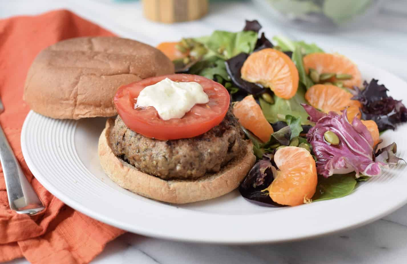 Beef and mushroom burger topped with tomato on plate with salad.
