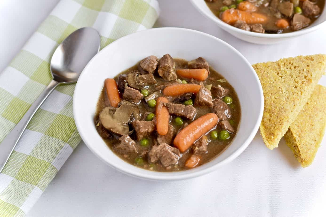 Gluten-free, low-carb slow cooker Beef and mushroom stew in a bowl with cornbread.