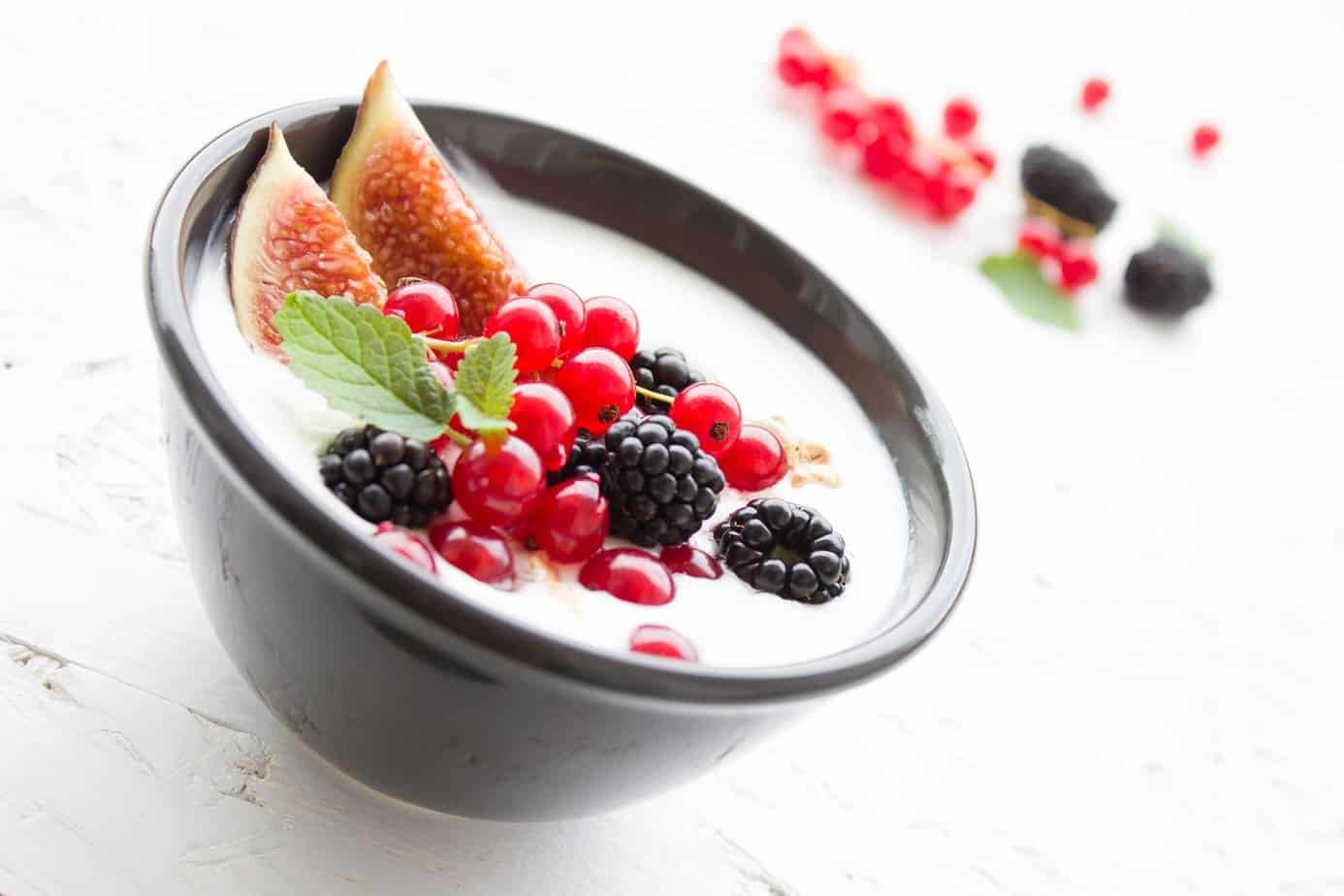 yogurt topped with berries and a fresh fig