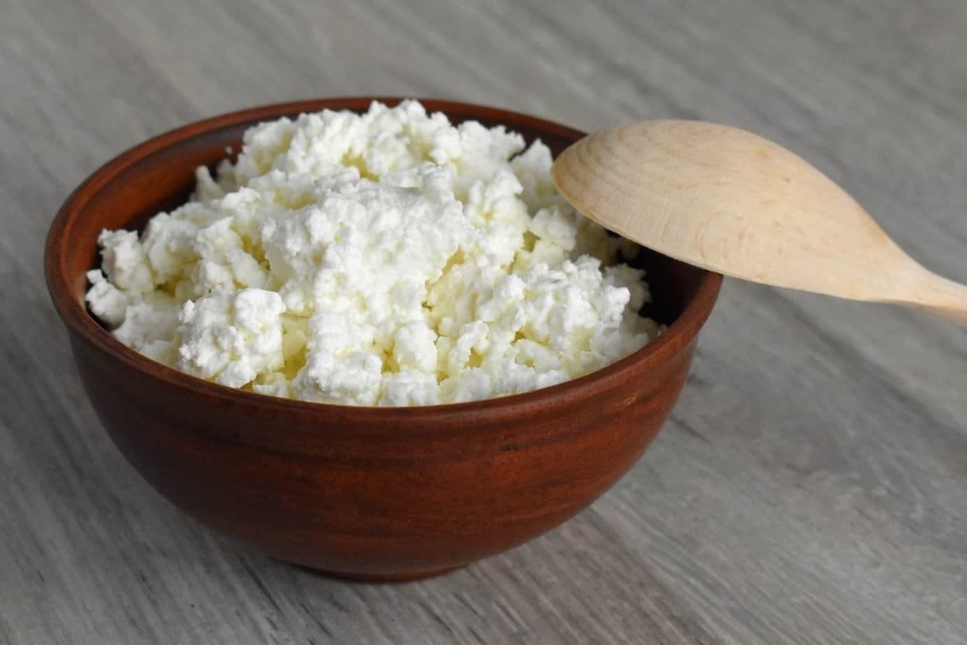 Bowl of cottage cheese with a wooden spoon.