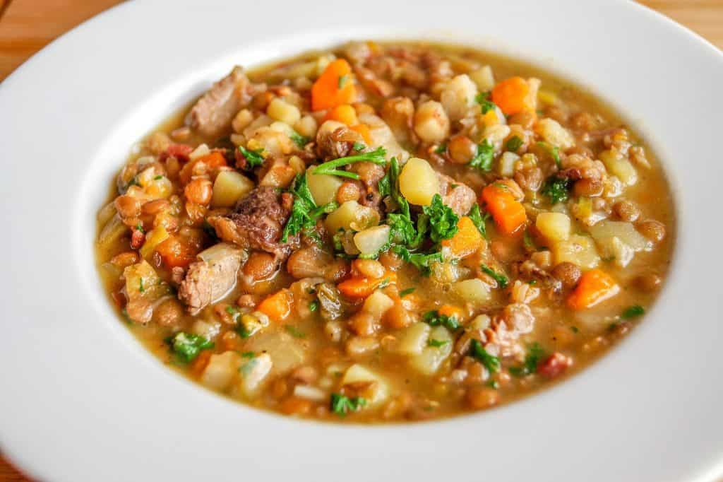 Lentil and vegetable soup in a large white soup bowl.