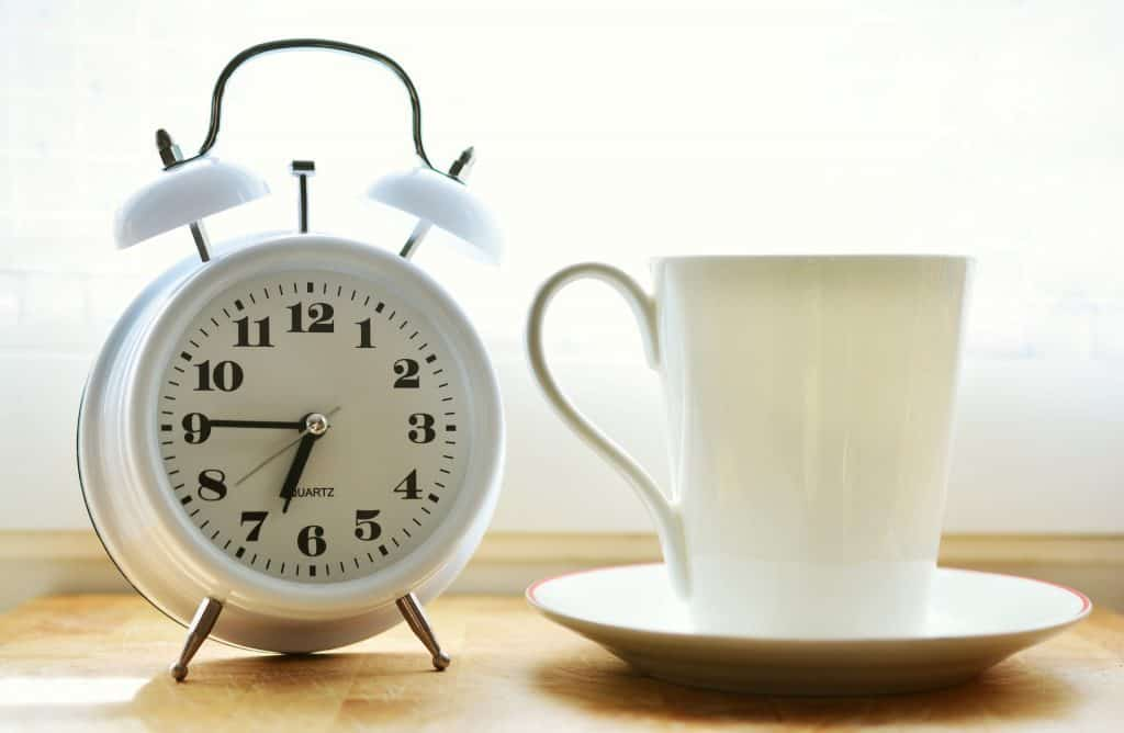 Alarm clock and coffee cup with saucer.