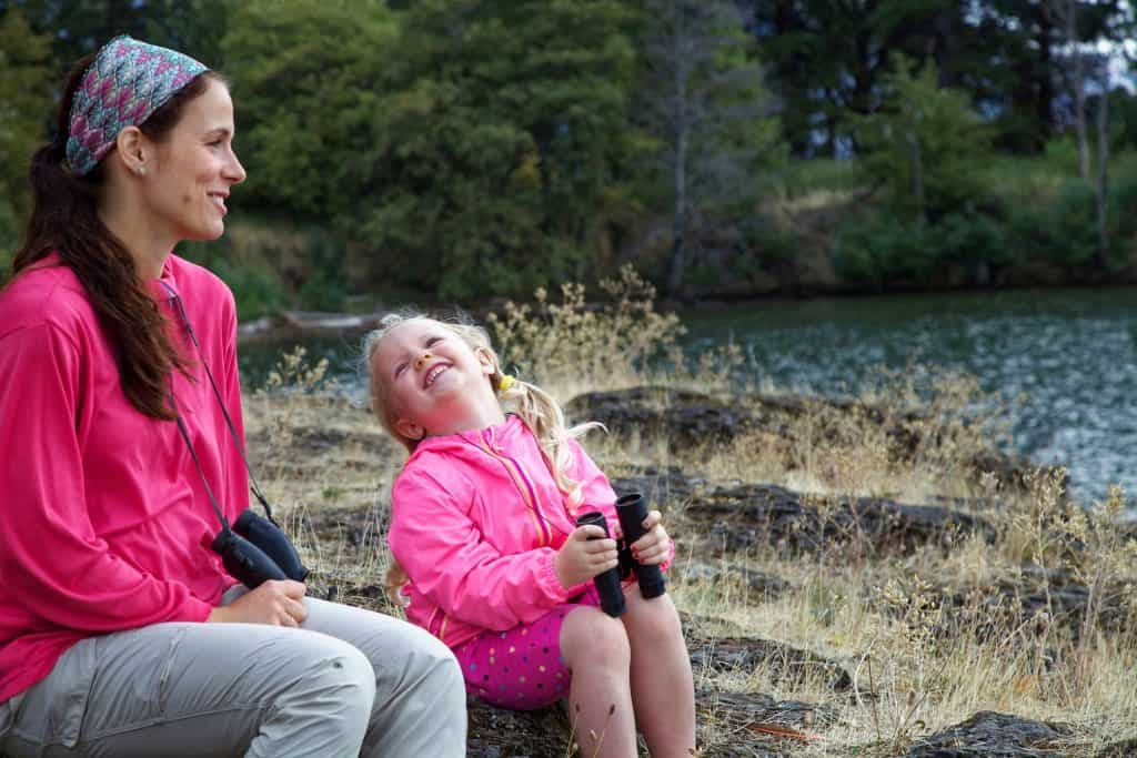 Mother and young daughter laughing outside with binoculars.