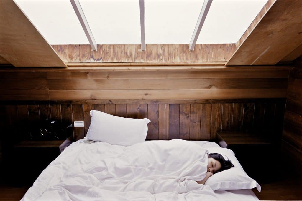 Woman sleeping in bed with white sheets.