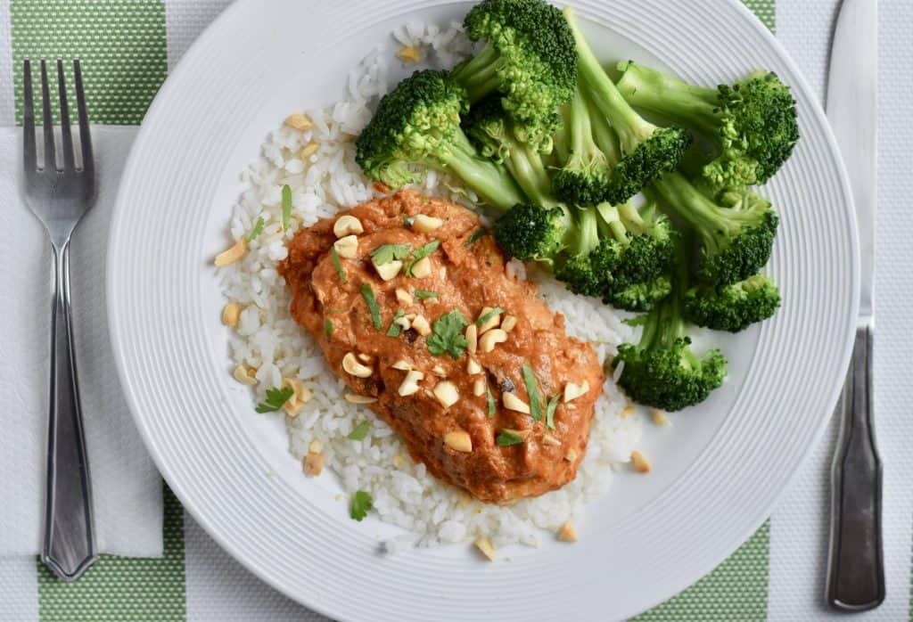 Thai peanut chicken breast on a bed of white rice served with cooked broccoli.