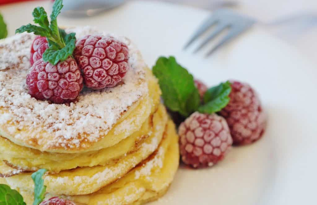 Pancakes with powdered sugar, and fresh raspberries