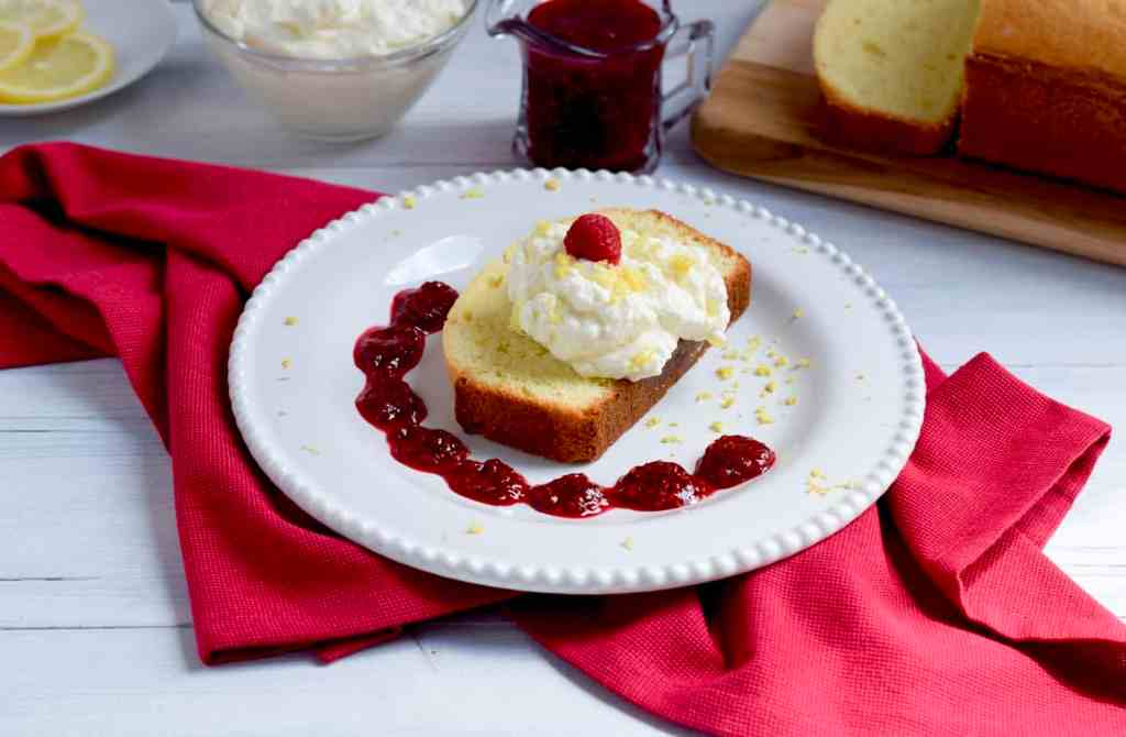 Lemon pound cake topped with whipped cream and a raspberry.