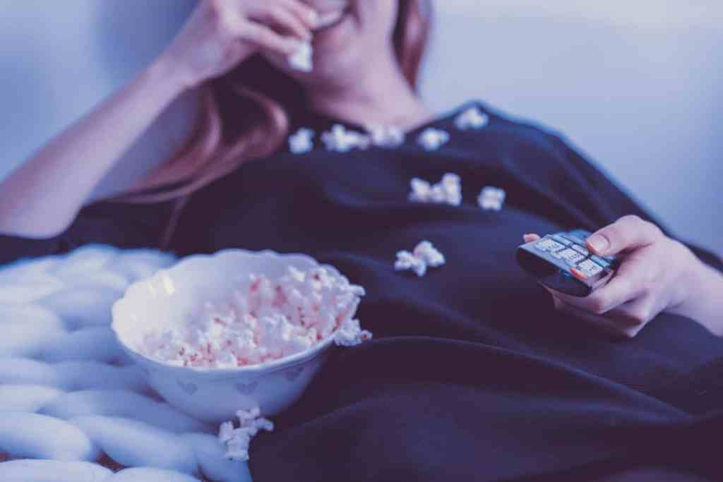 woman eating popcorn with remote control for TV in her hand